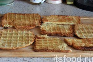 Повторяем процесс. Наши хлебцы получаются в 2 раза тоньше и намного легче исходного ломтя хлеба. Кроме того, они имеют сосем другой, не похожий на обычные сухари вкус. Горячие сухарики нельзя накладывать «валом». Они станут мягкими. Раскладываем их для остывания на большой доске.