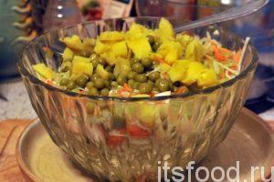 Загружаем заключительные компоненты салата капустного – это картофель кубиками и зеленый горошек. Посыпаем черным молотым перцем и осторожно пытаемся перемешать эту гору витаминов.